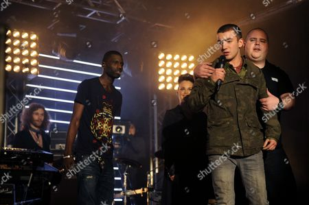 Jonny Clarke as Bart (R) rushes the stage while Wretch 32 performs