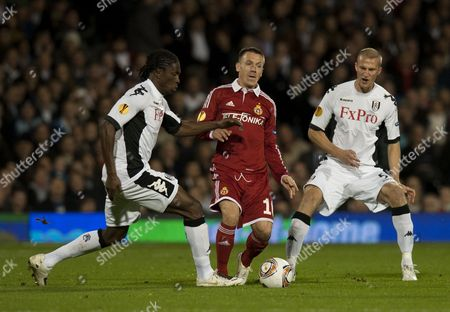 Dickson Etuhu and Brede Hangeland of Fulham try to get the ball off of Lukasz Gargula of Wisla Krakow