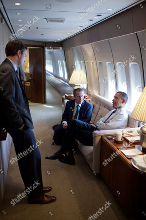 President Barack Obama talks with Principal Deputy Press Secretary Josh Earnest, left, and National Economic Council Director Gene B Sperling, centre, aboard Air Force One on the flight to Pittsburgh, Pennsylvania