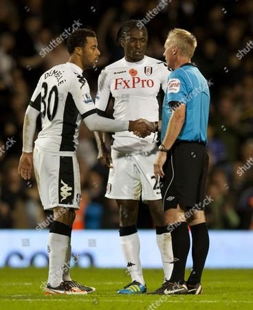Moussa Dembele of Fulham shakes hands with Referee Peter Walton as Dickson Etuhu looks on
