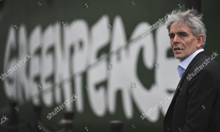 John Sauven, the Executive Director of Greenpeace next to the environmental organisation's flagship, Rainbow Warrior, after making her maiden voyage from Amsterdam