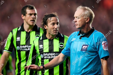 Referee Peter Walton is confronted by Gordon Greer and Mauricio Taricco of Brighton and Hove Albion