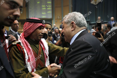 Jordanian Prime Minister Awn Shawkat Al-Khasawneh (R) is greeted after he won the vote of confidence