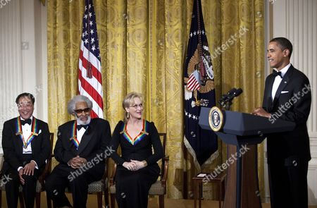 Musician Sonny Rollins (2L) and actress Meryl Streep (2R) listen as United States President Barack Obama (R) speaks
