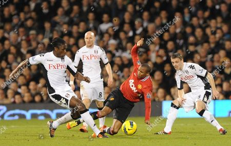 Ashley Young of Manchester United suffers an injury which forced him off after this clash with Dickson Etuhu of Fulham