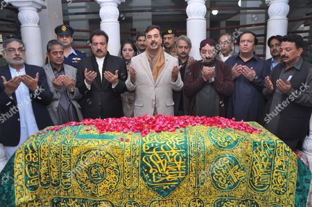 Pakistan Prime Minister Yousaf Raza Gillani (C) prays at the grave of assassinated prime minister Benazir Bhutto
