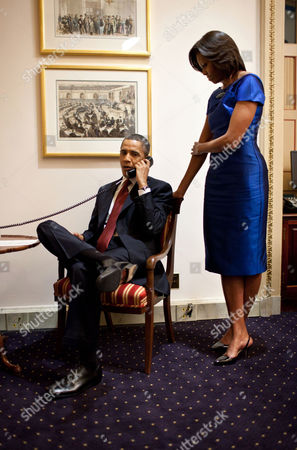 President Barack Obama informs John Buchanan that his daughter Jessica was rescued by U.S. Special Operations Forces in Somalia, First Lady Michelle Obama stands behind