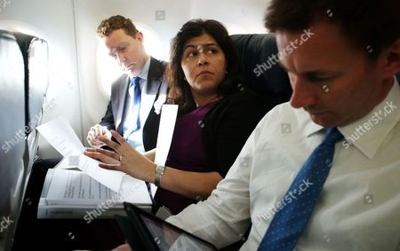 Sayeeda Warsi going through her speech on the flight to Rome with Secretary of Culture and Sport Jeremy Hunt (right) and Gregory Barker