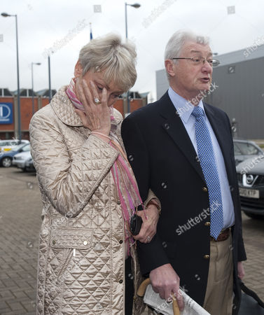 Elaine Tappin wiping a tear from her eye as she and her husband Christopher Tappin speak to the media outside Heathrow Police station before Christopher Tappin surrendered himself for extradition to the the USA.