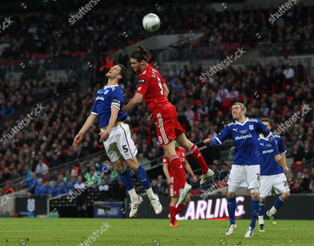 Andy Carroll of Liverpool is stopped by Mark Hudson of Cardiff City as Kevin McNaughton and Ben Turner of Cardiff City look on