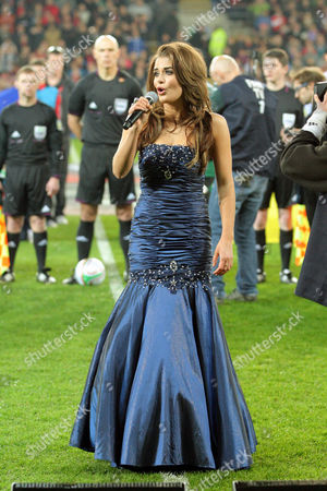 Welsh model Courtenay Hamilton singing the National anthem of Wales before kick off