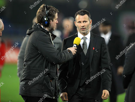 Ryan Giggs of Manchester United (R) interviewed for radio during half time