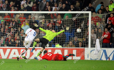 A shot by Kenny Cunningham of Costa Rica (L) hits the post