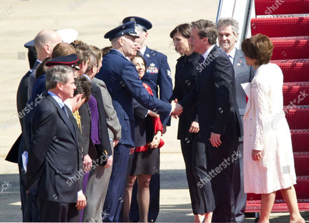 Samantha and David Cameron are greeted by officials including US Chief of Protocol, Capricia Marshall (R)