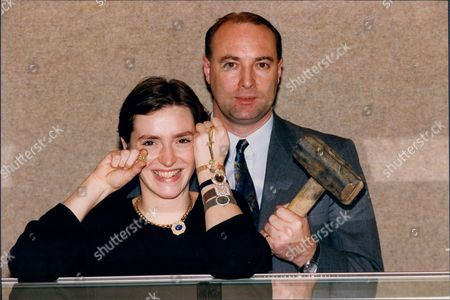 Jessica Thomas Of Christies Holding A A50 000 Yellow Diamond Miniature Gold Shotgun Is Pictured With D I Richard Leech. Just Some Of The Jewellery Items Recovered From The A30million Knightsbridge Safe Deposit Robbery.