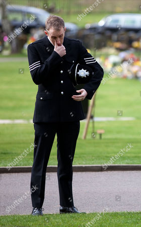 A mourning policeman wipes away a tear as the funeral is relayed via speakers, outside Stafford Crematorium