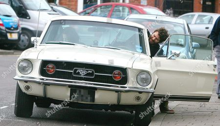 Stock Image of Howard Donald gets into his classic Ford Mustang Gt