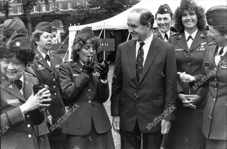 Defence Secretary George Younger Smiles As Captain Miriam Michael - A Pilot And Reserve Traffic Controller - Applies Her Lipstick - She Was One Of The Women Reserve Officers Representing Nato Attending A Conference.