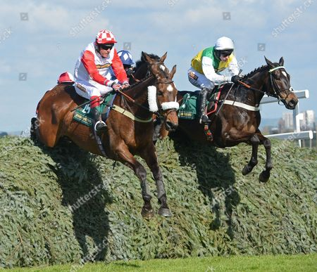 (R) Cloudy Lane (Richard Harding) takes The Chair Fence before going on to win The John Smith's Fox Hunters' Steeple Chase from (L) Launde (Mr. A. Ward-Thomas) on the first day of The Aintree Racecourse Grand National meeting.