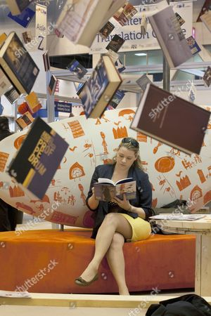 Charlotte Carey from the University of Plymouth Press reads a book at London Book Fair