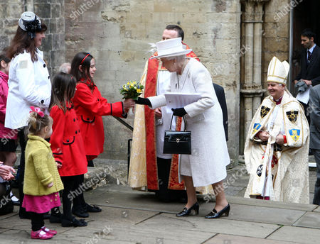 Queen Elizabeth II receives a bouquet from 10-year-old Lydia Lisk as she leaves Llandaff Cathedral