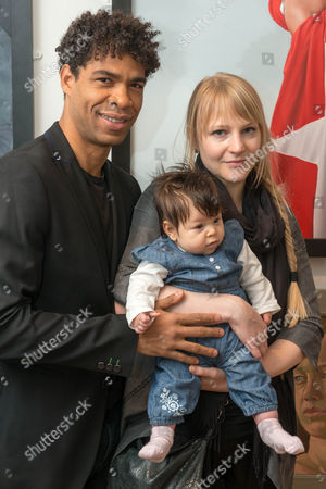 ballet dancer Carlos Acosta with his fiancee charlotte Holland and daughter and the portrait of him by Nigel Cox