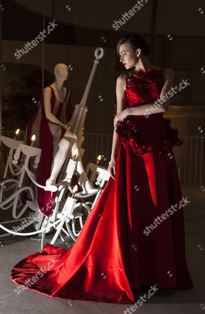 Stock Image of Model Zhanna Emelyanova in a sumptuous red silk satin ballgown from Giles Deacon's current collection