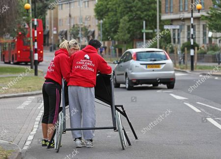 Eddie Kidd With His Wife Sammi Kidd (baseball Cap) And Friend And Helper Susan Taylor As They Approach The Eleven Mile Marker On The Route Of The London Marathon.