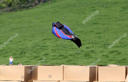 Gary Connery flying through the air in his wingsuit and coming into land on a pile of boxes