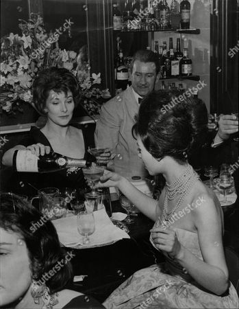 Adrienne Corri Pours Champagne For Customers At Gala Charity Night At 19th Club Adrienne Corri (born 13 November 1930) Is A Scottish-born Actress Of Italian Parentage. Despite Having Significant Roles In Many Films Adrienne Corri Is Likely To Be Remembered For One Of Her Smaller Parts That Of Mrs. Alexander The Wife Of The Writer Frank Alexander In The 1971 Stanley Kubrick Dystopian Film A Clockwork Orange. Though Not The Originally Cast For This Role She Was Brought In After The First Actress Left. Clad In An Eye Catching Bright Red Pajama Suit She Answers The Door To The Hero Of The Film Alex De Large And In A Scene Redolent With Black Humor And Violence Is Forcibly Stripped And Gang Raped Corri Being Thrust Center Stage In A Exuberant Quasi-theatrical Spectacle As Alex Accompanies The Stripping With A Joyful Rendition Of 'singing In The Rain'. Though The Scene Lasts Barely Three Minutes And Corri's Dialog Is Confined To Some Initial Preliminaries The Nature Of The Scene And The Manner Of Its Presentation Make It Perhaps The Most Memorable Scene In The Entire Film. Corri Appeared In Many Excellent Films Notably As Valerie In Jean Renoir's The River (1951) As Lara's Mother In David Lean's Dr. Zhivago (1965) And In The Otto Preminger Thriller Bunny Lake Is Missing . She Also Appeared In A Number Of Horror And Suspense Films From The 1950s Until The 1970s Including Devil Girl From Mars The Tell-tale Heart A Study In Terror And Vampire Circus. She Also Appeared As Therese Duval In Revenge Of The Pink Panther. The Range And Versatility Of Her Acting Is Shown By Appearances In Such Diverse Productions As The 1969 Science Fiction Movie Moon Zero Two Where She Played Opposite The Ever Dependable Character Actor Sam Kyd (len The Barman) And Again In 1969 In Twelfth Night Directed By John Sichel As The Countess Olivia Where She Played Opposite Alec Guinness (malvolio)