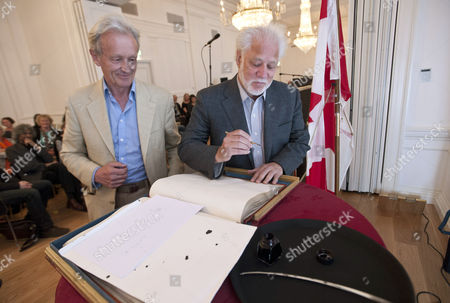 Royal Society of Literature President Colin Thubron presents author Michael Ondaatje with the RSL guest book