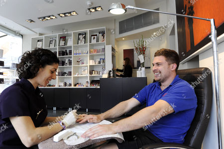 25-year-old electrician, Nathan Grant from Fulham is given a manicure by nail technician Maria Sanches at Margaret Dabbs Foot Clinic and Nail Spa in central London