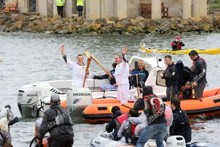 Matt Usher and Matt King carry the Olympic flame by boat over Rutland Water