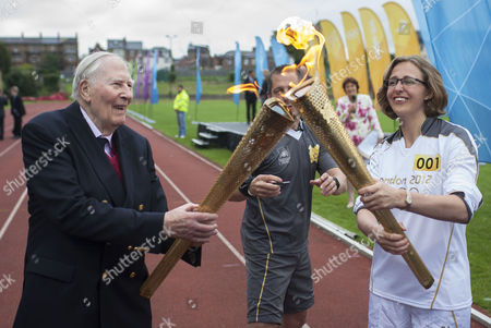 Sir Roger Bannister hands the torch over to Nicola Byrom, a student doctor at Oxford University