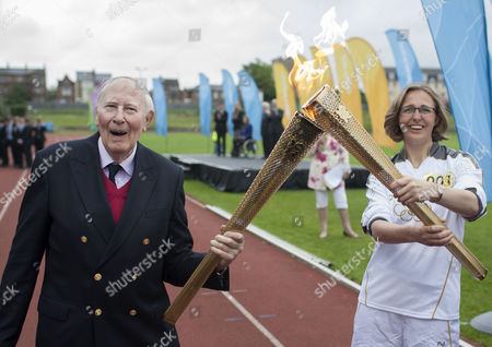 Sir Roger Bannister hands the torch over to Nicola Byrom, a student doctor at Oxford University.