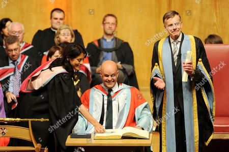 Stock Image of Mark Pollock, accompanied by his fiancee Simone George, receives his honorary degree from the QUB Vice Chancellor Peter Gregson