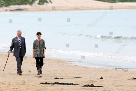 Prince Charles and the Duchess of Northumberland are seen walking along the beach at Dunstan Steads