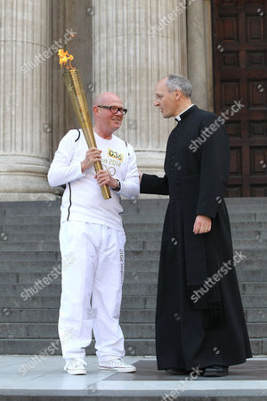Stock Picture of Torchbearer and the Dean of St Paul's Cathedral, Right Reverend Graeme Knowles, on the steps of St Paul's Cathedral
