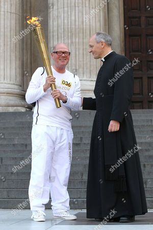 Torchbearer and the Dean of St Paul's Cathedral, Right Reverend Graeme Knowles, on the steps of St Paul's Cathedral
