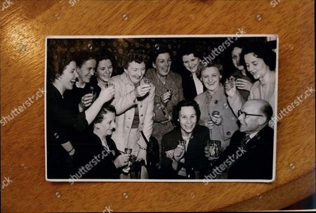 Stock Photo of Women's Royal Air Force Girls 49th Reunion Margaret Leighton (74) Vera Mortimer (77) Joan Foster (72) Madge Clarkson (70) Showing A Picture Of Them In 1949