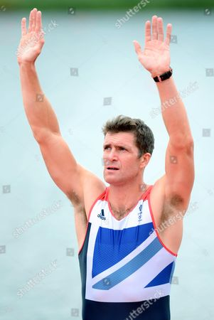 Great Britain's Greg Searle salutes the crowd as he awaits to be presented with a bronze medal as part of the Mens Eight crew