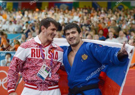 Tagir Khaibulaev of Russia celebrates winning a Gold medal in the Judo 100kg category with coach, Nikolai Petrov