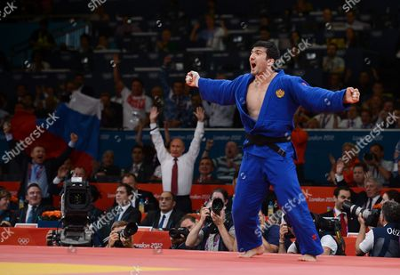 Vladimir Putin, President of Russia (white shirt, standing) celebrates as Tagir Khaibulaev of Russia wins the Gold medal in the Judo 100kg category as part of the London 2012 Summer Olympic Games, Excel Arena