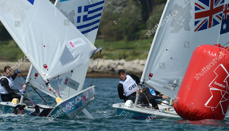New Zealand get a dunking in the Olympic Laser sailing race at Portland. Team GB Paul Goodison watches as Andrew Murdoch partly capsizes at the windward mark and is dunked under the water.
