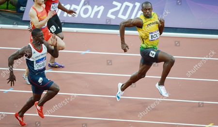 Jamaica's Usain Bolt looks back at Team GB's Dwayne Chambers as Bolt wins his semi-final heat in the men's 100m