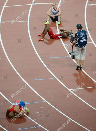 Fourth placed Dai Greene of Great Britain looks on as Gold medalist Felix Sanchez celebrates winning the Men's 400m final