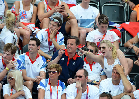 Stock Image of David Carry, finance of Keri-Anne Payne sits inbetween British Prime Minister David Cameron and Rebecca Adlington as they cheer on Keri-Anne Payne during the Women's 10k Marathon Swimming also in picture is Sir Steve Redgrave (sitting in front of Rebecca Adlington)