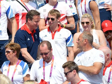 David Carry, finance of Keri-Anne Payne (centre) and Rebecca Adlington look on as Prime Minister, David Cameron shakes hands with Sir Steve Redgrave