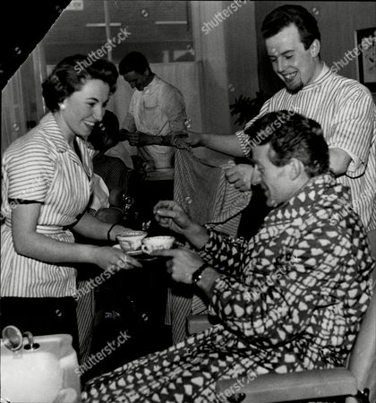 Stock Picture of Comedian Jon Pertwee Receives A Cup Of Tea From Manicurist Barbara Daley While He Has His Hair Done By Alan Cooke.