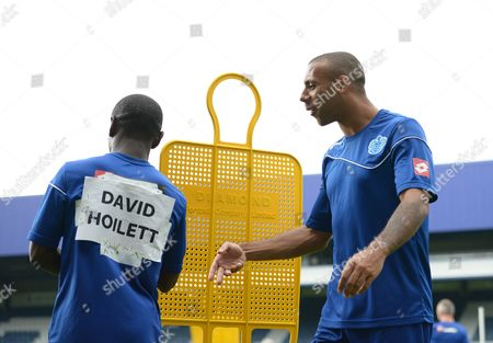 Anton Ferdinand of Queens Park Rangers jokes with Shaun Wright-Phillips who has the name David Hoilett taped to his training shirt during an open training session